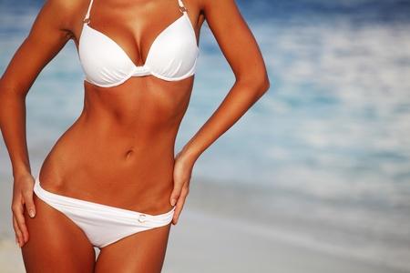 beach model: woman in bikini on sea background