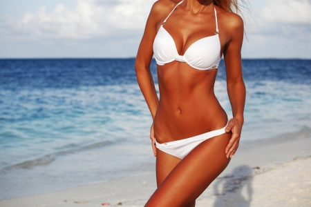 hot girl legs: woman in bikini on sea background