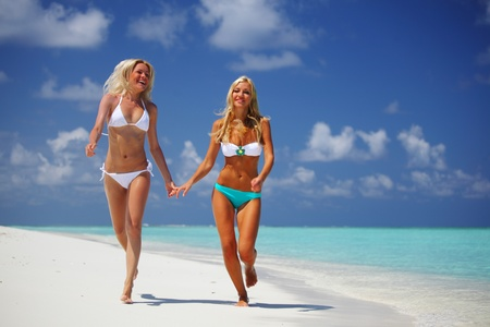 women in bikini: Two girls run along the ocean coast