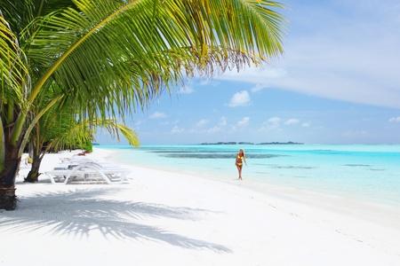 donna in bikini sotto palma sullo sfondo del mare