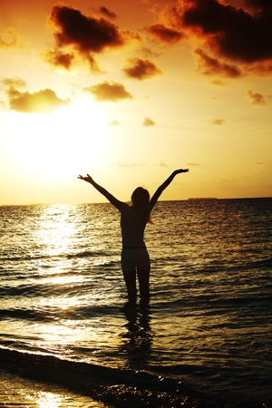 sexy woman silhouette: happy woman standing on a sunset in ocean waves Stock Photo