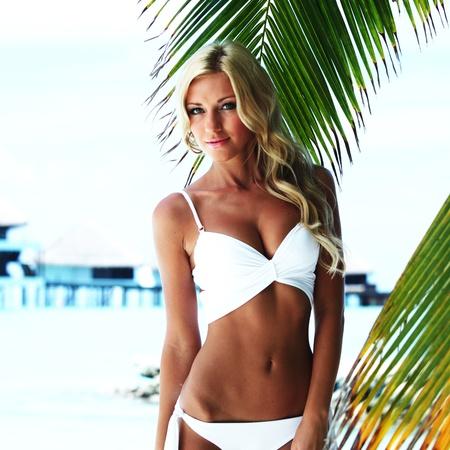 hot girl lying: woman in bikini under palm on sea background Stock Photo