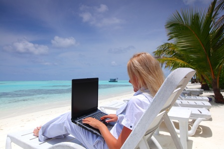 business woman with laptop lying on a chaise lounge in the tropical ocean coast Stock Photo - 11408767