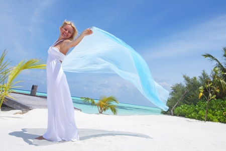 dress blowing in the wind: woman with a white fabric in his hands on the beach