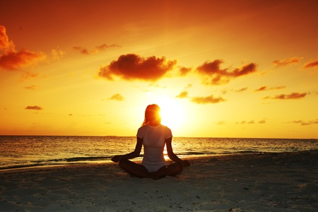yoga beach: sunset yoga woman on sea coast Stock Photo
