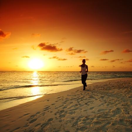 woman run along the sea coast of sunrise behind photo