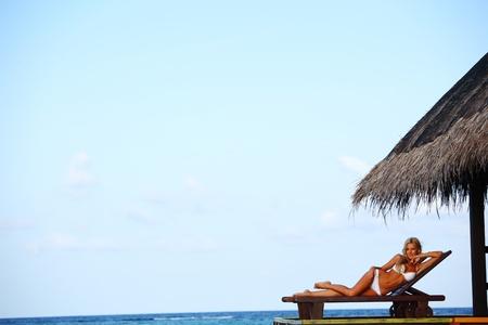 woman on lounge sea on background photo