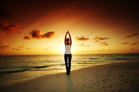 yoga sunset: sunset yoga woman on sea coast Stock Photo