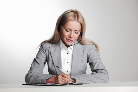 business woman in a headset writing in notebook Stock Photo - 11440777