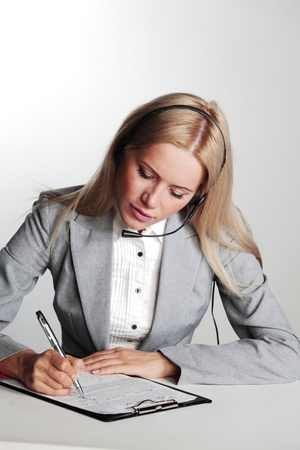 business woman in a headset writing in notebook photo