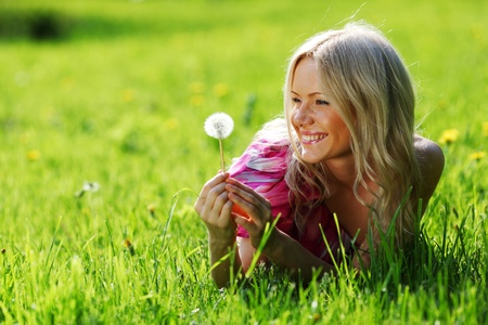 fuzzy: girl with a dandelion in his hand lying on the grass
