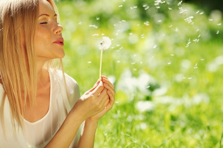 girl blowing on a dandelion lying on the grass photo