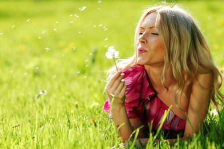 meisje blazen op een paardebloem liggend op het gras