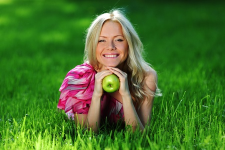 blonde holding an apple in his hand lying on green grass Stock Photo - 11951190