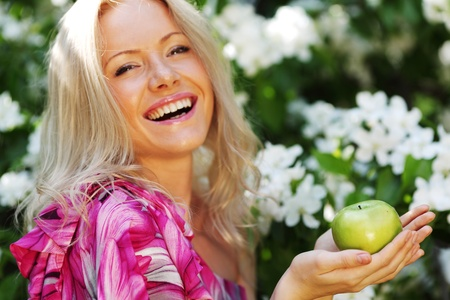 girl with green apple on a background of white flowers Stock Photo - 11951381