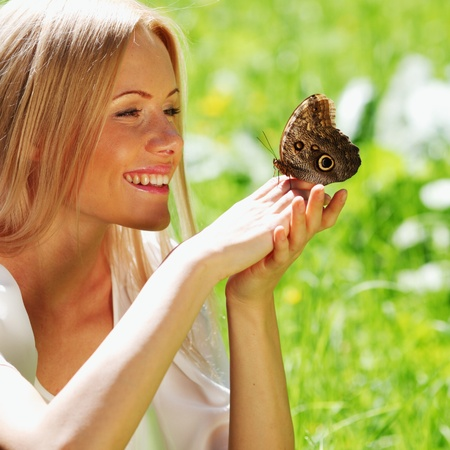 Woman playing with a butterfly on green grass Stock Photo - 11949624