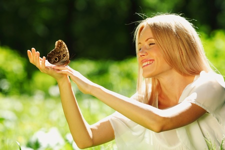 Woman playing with a butterfly on green grass Stock Photo - 11949976