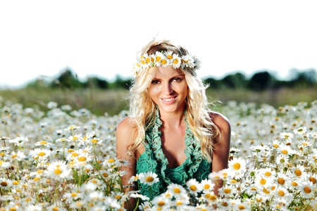 spring holiday: beautiful girl on the daisy flowers field