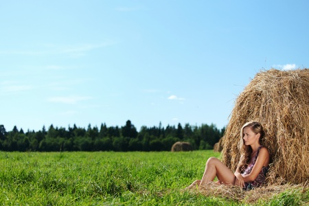 portrait of a girl next to a stack of hay under the blue sky Stock Photo - 11951469