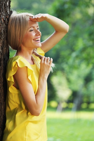 happy woman posing against a background of trees photo
