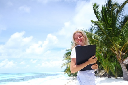 business woman on ocean coast on the background of a palm trees and sky and sea photo