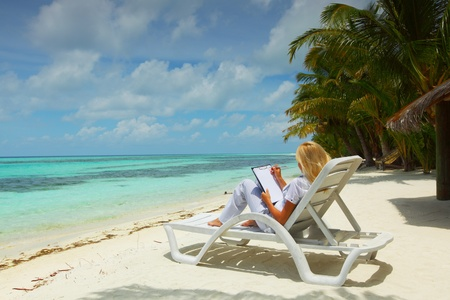business woman with blank paper lying on a chaise lounge in the tropical ocean coast photo