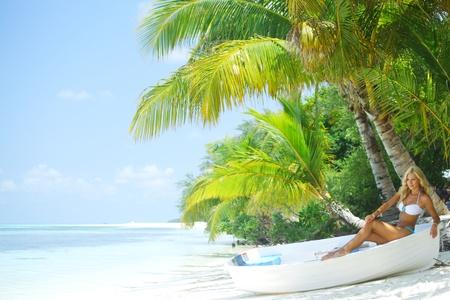 woman in boat under palm on sea background photo