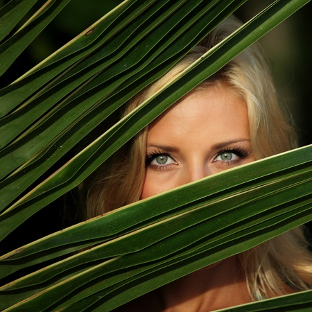 bliss: woman hiding behind the palm leaves