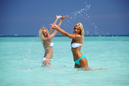 wet girl: Two girls playing in ocean water Stock Photo