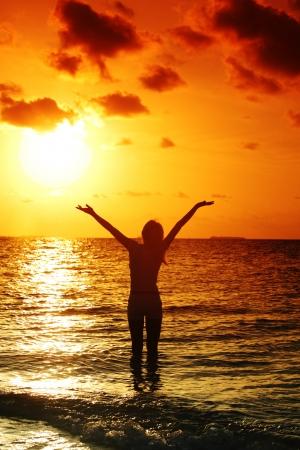 happy woman standing on a sunset in ocean waves Foto de archivo