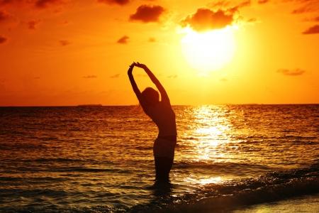 glückliche Frau, die auf einem Sonnenuntergang im Ozean Wellen