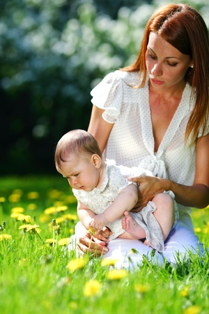 family garden: Happy mother and daughter on the green grass Stock Photo