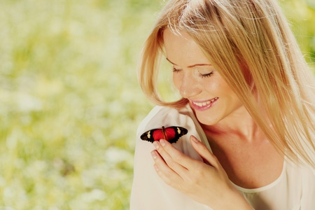 Woman playing with a butterfly on green grass Stock Photo - 12040762