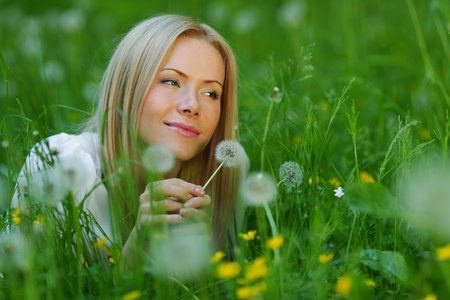 girl with a dandelion in his hand lying on the grass Stock Photo - 12040777