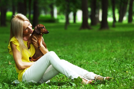 woman dachshund in her arms on grass Stock Photo - 12040662