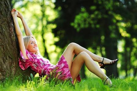 glückliche Mädchen liegen unter einem Baum an einem Sommertag