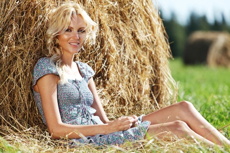 portrait of a girl next to a stack of hay under the blue sky Stock Photo - 12041251