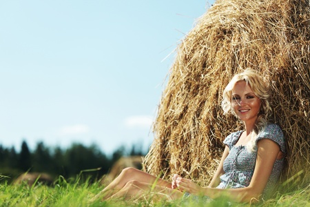 clothing model: portrait of a girl next to a stack of hay under the blue sky