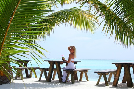 woman sitting in a tropical cafe on the background of a  palm trees and sky and sea Stock Photo - 12079729