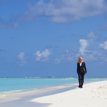 business woman with briefcase walking on the desolate ocean coast Stock Photo - 12079872