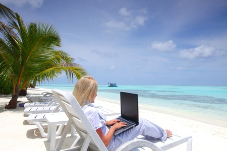 business woman with laptop lying on a chaise lounge in the tropical ocean coast Stock Photo - 12079766
