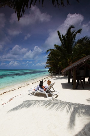 business woman with laptop lying on a chaise lounge in the tropical ocean coast Stock Photo - 12079848