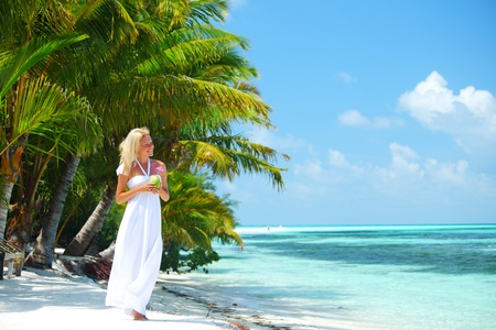 woman with a coconut cocktail on a tropical shore photo