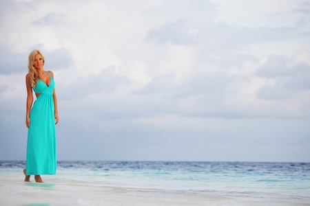 woman in a blue dress on the ocean coast Stock Photo - 12079878