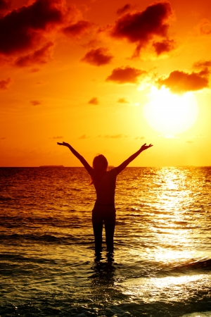 happy woman standing on a sunset in ocean waves Stock Photo