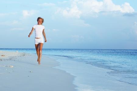 happy girl run along the ocean coast photo