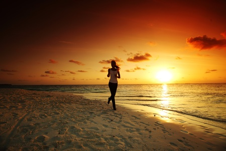 woman run along the sea coast of sunrise behind Stock Photo - 12079760