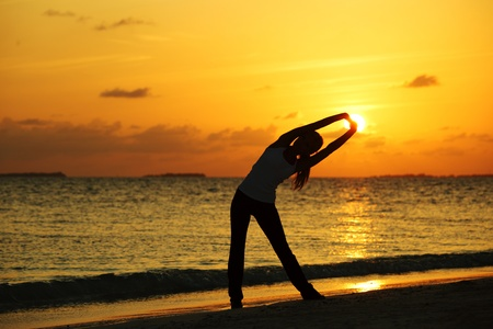 sunset yoga woman on sea coast Stock Photo - 12079841