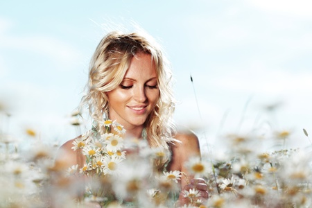beautiful girl on the daisy flowers field
