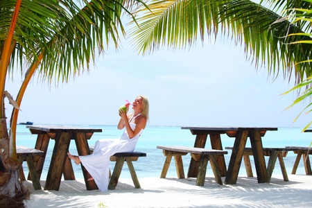 woman sitting in a tropical cafe on the background of a  palm trees and sky and sea Stock Photo - 12451877